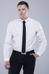 Young handsome man in a shirt with a tie on a light gray background