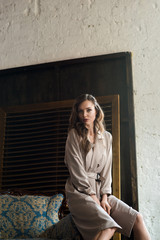 trendy woman in classic trench coat posing on armchair