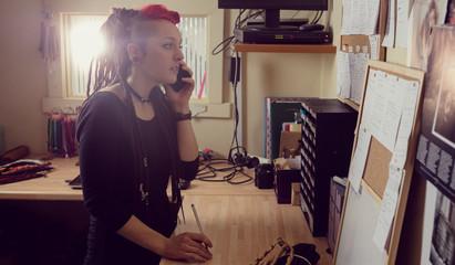 Female hairdresser talking on mobile phone