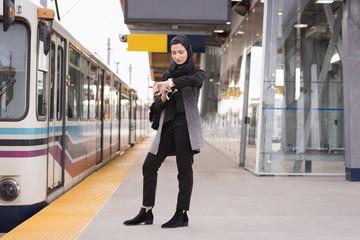 Woman in hijab using smartwatch