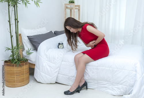 f06d1402ac Beautiful young Asian woman in red casual dress suffering from stomach ache
