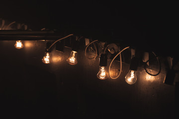 Old style garland of vintage tungsten bulb lamps
