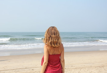 A beautiful girl with blond hair, in a red dress looks at the sea and stands with her back. Summer girl on the sea. Tenderness, alone with nature, pacification