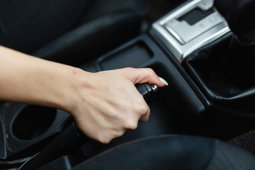 Close up of female hands holding a handbrake lever to keep the vehicle stationary. The girl puts the car in the Parking lot with the handbrake.