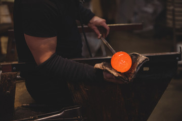 Glassblower shaping molten glass piece with a wet cloth