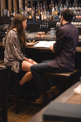 Couple looking at menu at bar counter