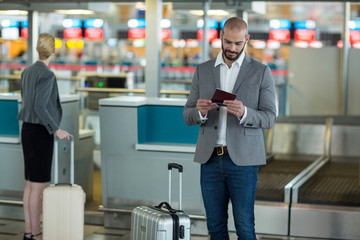 Businessman with luggage checking his boarding pass