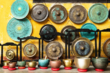 Gongs and singing bowls - traditional Asian musical instruments on a street market. Hoi An, Vietnam.