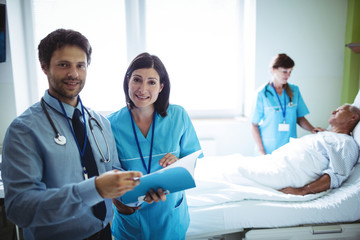 Male doctor and nurse interacting over a report