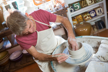Happy male potter making pot