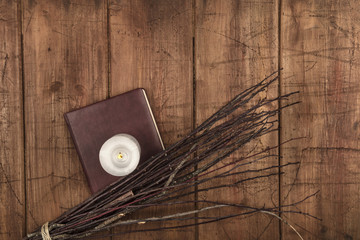 An overhead photo of a handmade broom with a candle, a grimoire, and copy space