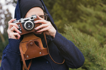 Young woman in hoodie holding retro photo camera and taking photo in the forest.  Spring nature on background.