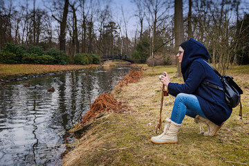 Young blonde woman in hoodie holding retro photo camera and making photo of ducks on the river. Spring nature concept. Outdoor portrait