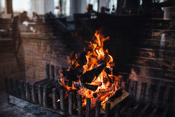 Colourful flame and burning wood at fireplace. Close up shot of bright flame which gives heat. Blazing woods and coals. Dark background image