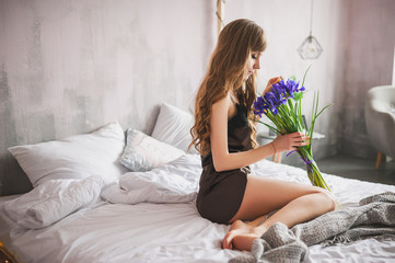 Beautiful woman in brown nightie lying on the bed and a bouquet of flowers.