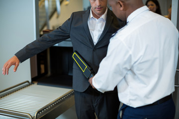 Airport security officer using a hand held metal detector to check a commuter