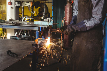 Welder welding a metal in workshop