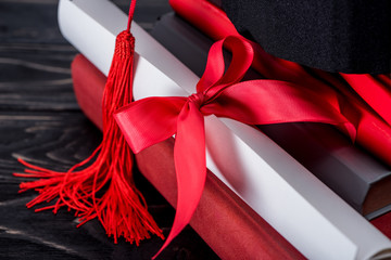 Graduation hat and diploma with red ribbon on stack of books