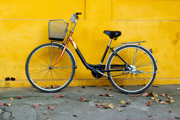 Old bicycle on a background of bright painted yellow wall and autumn leaves on a street.