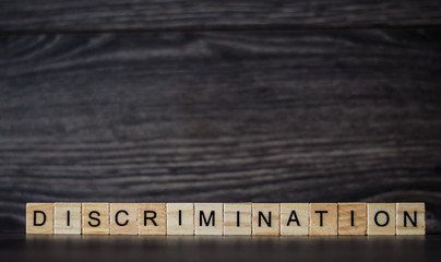 the word discrimination, consisting of light wooden square panels on a dark wooden background