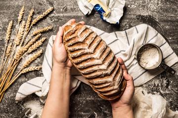 Rustic crusty loaf of bread in baker 's hands on black