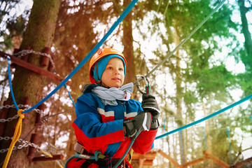 little boy climbing in adventure activity park