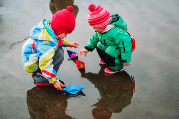 little girls play with paper boats in spring water