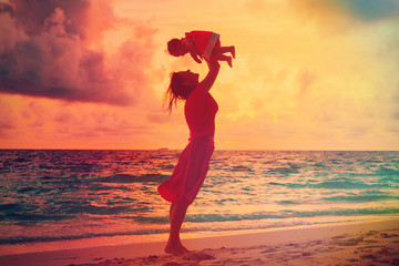 mother and daughter having fun at sunset beach