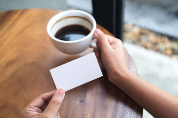 Hands holding an empty business card and coffee cup