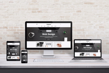 Multiple display devices with modern flat design web site presentation. Wooden desk and brick wall...