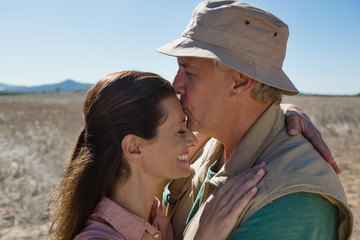 Man kissing woman forehead on landscape