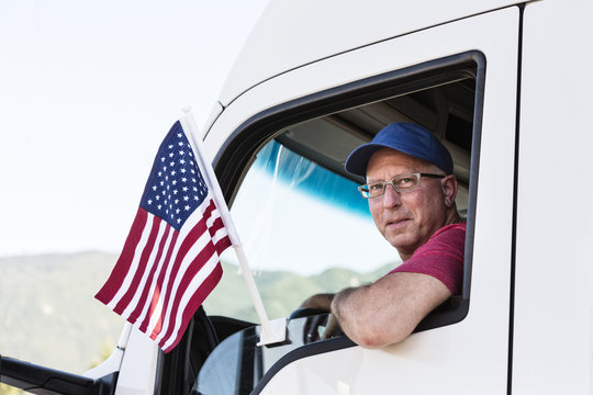 Caucasian man truck driver in the cab of his truck with an American Flag attached to the window.