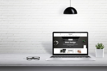 Laptop with modern web site presentation. Free space for text beside on white brick wall.