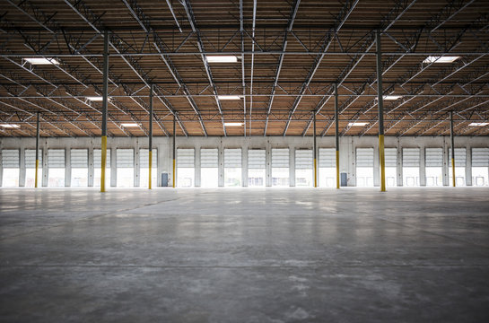 Wide angle interior view of large empty warehouse and loading dock doors