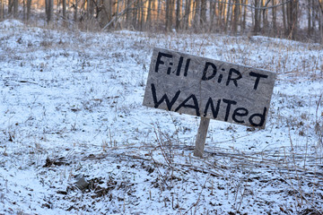 'Fill-Dirt Wanted' sign in a snowy field.