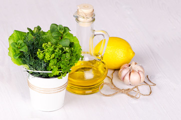 Fresh herbs in a bucket with lemon and olive oil on a light wooden background