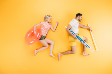 happy young couple holding beach umbrella and swimming ring on yellow, summer vacation concept Wall mural