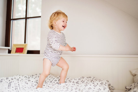 Cute toddler boy jumping on the bed.