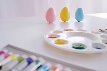 preparing for Easter. Painting easter eggs on colorful tablecloth background.