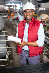 Smiling male employee noting about products in juice factory
