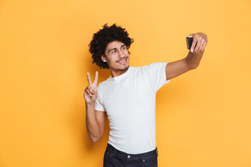 Portrait of a smiling young african guy taking a selfie