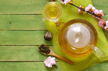 Green tea in a teapot with a branch of cherry blossoms