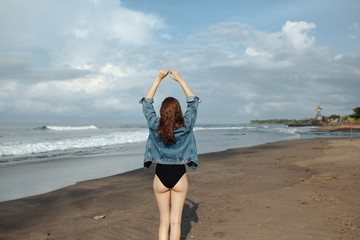 Rare veiw brunette Woman wearing black swimsuit and denim jacket at ocean background enjoy walking at beach, hands raised up to the sky. Freedom concept