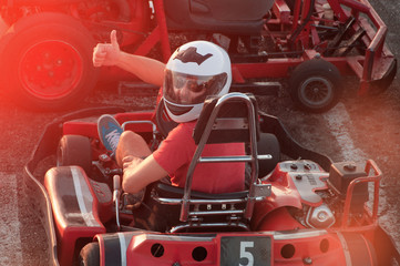 Men driving Go-kart car with speed in a playground racing track.