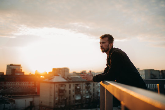 Young man is pondering on terrace of roof against background of cityscape at sunset.
