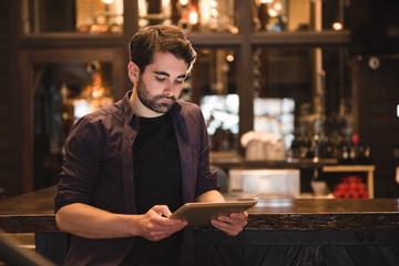 Man using digital tablet at bar counter