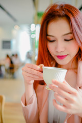 Portrait of beautiful woman holding a cup of coffee in her hand on blur background coffee shop