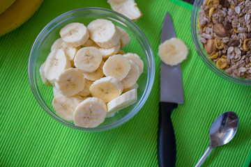 tasty fresh bananas and sliced banana in the bowl, top view.