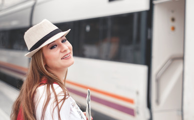 Traveler girl with map, hat and backpack walking train on railway platform.