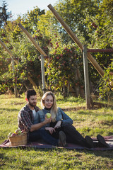 Happy couple together sitting on a blanket in apple orchard